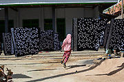 A group of school girls run through beautiful batik tulis (handmade batik)as it hangs to dry in Podhek Village on the island of Madura. The entire village produces batik of the finest quality and most vibrant colors by using a batik process of applying wax and dyes to fabric to create intricate and detailed designs by hand.