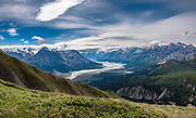 Kluane National Park and Reserve, St. Elias Mountains, Yukon, Canada. Hike Sheep Creek trail (10-15 km with 500-1200 m gain or 1700-4000 ft) for spectacular views of the Slims River Valley and surrounding St. Elias Mountains, plus Kluane Lake seen from Soldier's Summit on Tachal Dahl (Sheep Mountain) Ridge. In a startling case of global warming, over 4 days in spring 2016, the Slims River suddenly disappeared, leaving windswept mud flats creating clouds of dust in the formerly clear air. With its main water supply cut off, Kluane Lake will be isolated within a few years, shrinking below its outflow into the Kluane River (which flows into the Donjek River, White River, Yukon River, and eventually the Bering Sea). Kluane Lake chemistry and fish populations are rapidly changing. For the last 300 years, abundant meltwater from the Kaskawulsh Glacier has been channeled by ice dam to drain via the 150-meter wide Slims River, north into Kluane Lake. Between 1956 and 2007, the Kaskawulsh glacier retreated by 600-700m, which most scientists attribute to anthropogenic climate change. Meltwater flooding from accelerating retreat in 2016 carved a new channel through a large ice field, diverting all flows to the Kaskawulsh River, a tributary of the Alsek, which flows into the Gulf of Alaska. This image was stitched from multiple overlapping photos.