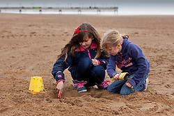 © Licensed to London News Pictures.09/04/2012, Skegness, North Lincolnshire, UK. Bank Holiday Monday weather, Skegness sea front. Pictured, Erin Smith (7), right and Kayley Robinson-Vaughan (11), who had travelled down from Yorkshire, brave the high winds and rain to play in the sand on the beach at Skegness. Photo credit : Dave Warren/LNP