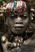 Young girl with face and body painted, shell and beaded head gear, Mursi Tribe, Mago National Park, Lower Omo Valley, Ethiopia, portrait, person, one, tribes, tribal, indigenous, peoples, Southern, ethnic, rural, local, traditional, culture, primitive,
