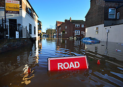 © Licensed to London News Pictures. 27/12/2015. York, UK.  A road sign is almost completely submerged by floodwater in York City centre. Large areas of the North of England have been hit by severe flooding following unusually heavy rainfall in December. Photo credit: Ben Cawthra/LNP