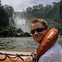 South America, Argentina, Iguacu Falls. Tourist on boat excursion at base of Iguacu Falls.