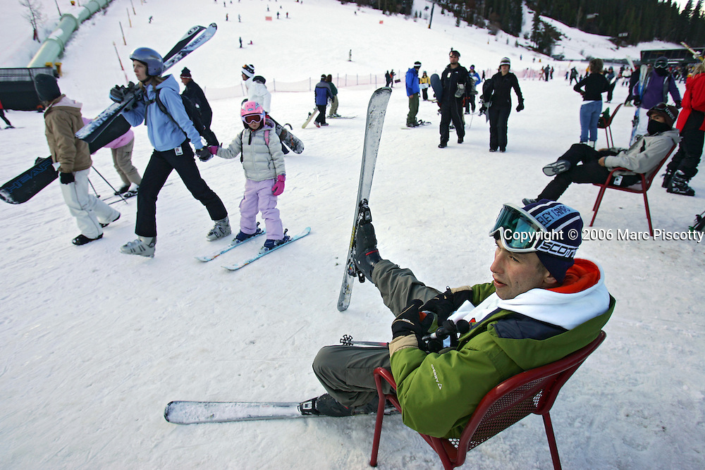 Vito Zigic (in chair), 27, of Chicago, Ill. sits in a chair with his skis on while waiting for a group of friends at the base of Winter Park Resort on Wednesday November 22, 2006. Winter Park and the other ski areas in Colorado are preparing for the influx of skiiers and snowboarders that have historically taken advantage of the the snow over a long Thanksgiving weekend. Zigic said he and his friends are up skiing for six days and that it was his first time ever skiing..(MARC PISCOTTY/ © 2006)
