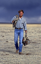 sexy rancher walking on a field as a storm approaches