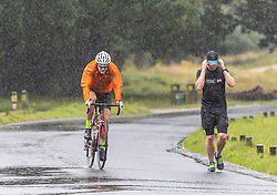 Licensed to London News Pictures. 07/08/202. London, UK. Summer washout. A runner and cyclist get caught in torrential rain in Richmond Park, southwest London today as thunderstorms continue to hit the South East with further showers expected tomorrow. Yellow weather warnings for England have been issued for thunderstorms with heavy rain, and possible flooding as the bad weather is set to continue until Monday. However brighter weather is finally forecast for next week with highs of 23c. Photo credit: Alex Lentati/LNP