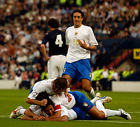 Photo: Jed Wee.<br />Scotland v Italy. FIFA World Cup Qualifying match. <br />03/09/2005.<br /><br />Italy's Fabio Grosso (bottom) is mobbed as he scores the equalising goal.
