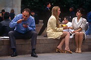 Nineties office workers in the Square Mile - the capitals financial district - eat lunch outside, on 21st June 1997, in Broadgate, London, England.