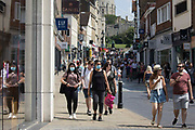 Shoppers and visitors, some of whom wearing face coverings, are pictured close to Windsor Castle on Freedom Day, when the UK government lifted almost all remaining Covid-19 restrictions in England, on 19th July 2021 in Windsor, United Kingdom. Social distancing restrictions have been removed and face coverings are no longer required by law, although their use is recommended in crowded and enclosed spaces. Cases of the coronavirus are now expected to surge across the UK, which currently has the highest rate of daily recorded Covid-19 cases in the world.