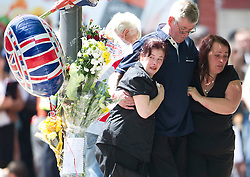 © London News Pictures. 26/05/2013. Woolwich, UK.  Mother and stepfather Lyn (right) and Ian Rigby (centre) at the scene. Family of murdered serviceman Drummer Lee Rigby visit the scene of his death in Woolwick, London. Drummer Lee Rigby was murdered by two men in Woolwich town centre in what is being described as a terrorist attack. Photo credit: Ben Cawthra/LNP
