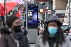 © Licensed to London News Pictures. 30/12/2020. London, UK. Members of the public walk past a Covid-19 information displays in Hammersmith, West London as the Oxford vaccine is approved for use with the UK ordering 100 million doses. Ministers are expected to roll out vaccinations from the 4 January 2021 as they mull over putting parts of the country into tier 5 restrictions to slow down the spread of the latest Covid-19 mutation which has increased infections in the capital. Last week Health Secretary Matt Hancock announced another new Covid-19 mutation has been discovered in the UK as Downing Street ordered many more areas of England to go into Tier 4 lockdown with tougher new Covid-19 restrictions for many as the mutated strains continue to spread throughout the UK. Photo credit: Alex Lentati/LNP