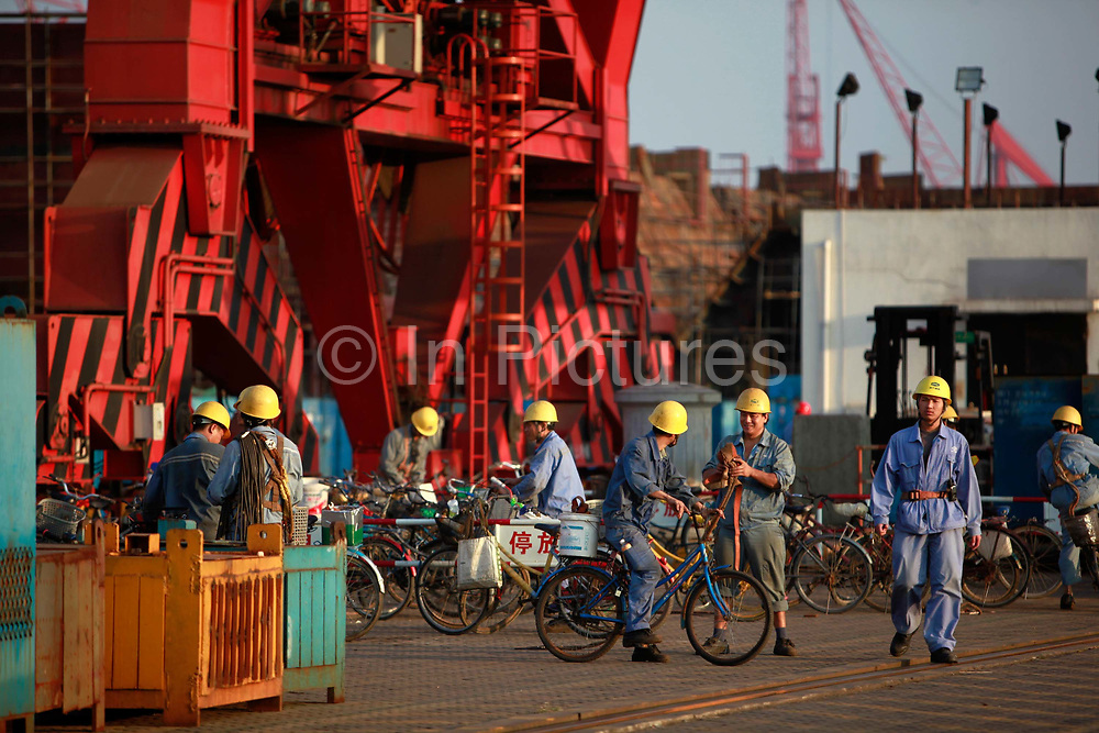 Workers ride their bikes after finishing their shift at the China State Shipbuilding Corp.'s (CSSC) Longxue Shipyard in Guangzhou, Guangdong Province, China, on Sunday, Nov. 13, 2011. China is the world's biggest shipbuilder, however recent economic downturns have caused a glut in supplies.