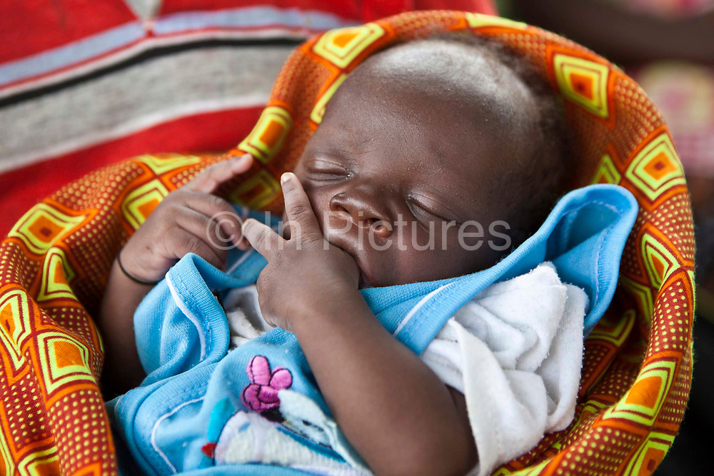 Deus a 2 weeks  old baby sleeps whilst waiting with her mother. Women from Kitahurira, the only Batwa tribe settlement in Mpungu district, wait with their children to attend the community out reach clinic. Bwindi Community Hospital provides several clinics every day in the local area. The mothers and children receive nutrition information and vaccinations from the hospital nurse. The Mpungu district is on the edge of the Bwindi Impenetrable Forest, Western Uganda.