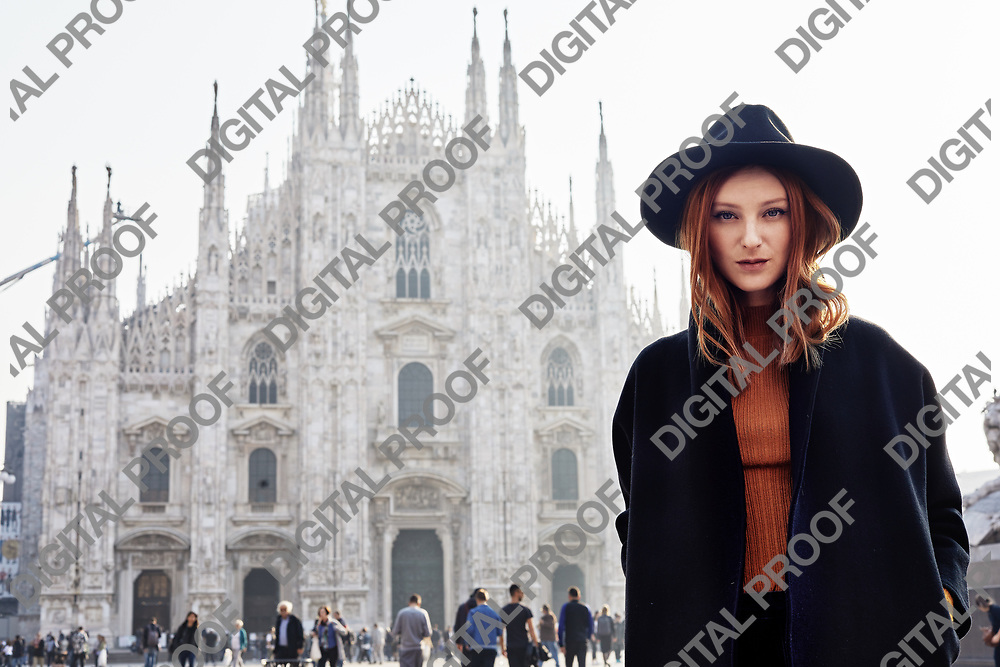 Fashion model wearing a hat and a dark coat in front of the Duomo of Milan in Italy in a October morning