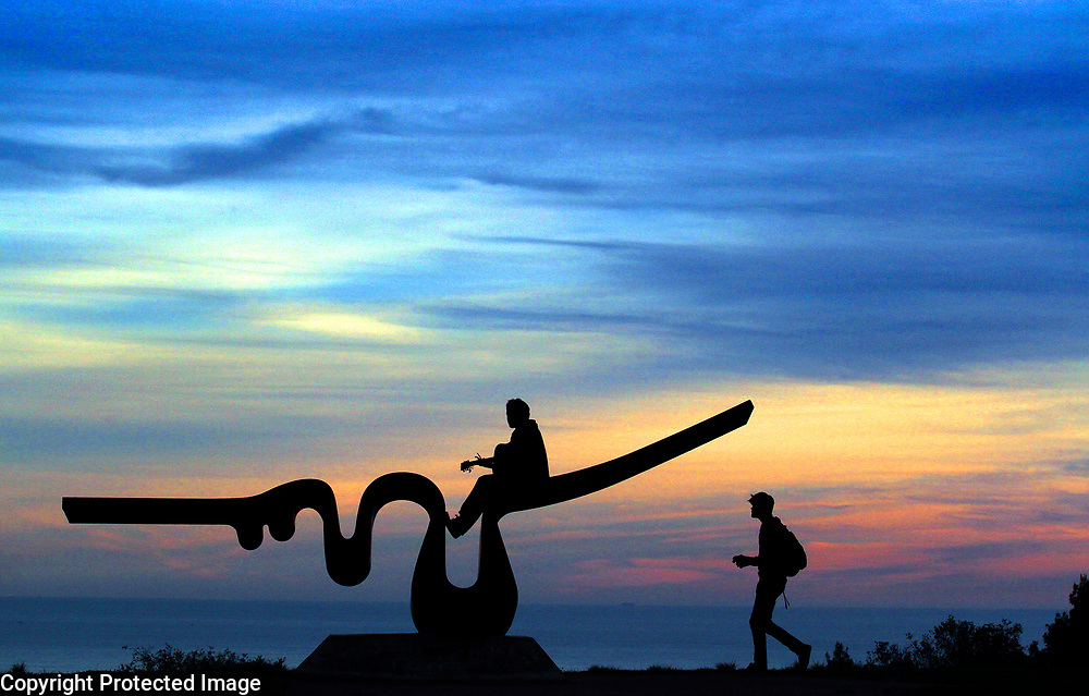 The sunset paints a striated pastel sky as Porter College student Austin James Hicks plays one of his original tunes atop Kenny Ferrell's 'Porter Wave' sculpture overlooking the Monterey Bay at UC Santa Cruz as a fellow student happens by on Tuesday. The sculpture was created as Ferrell's senior project in 1974 when he was a UCSC student.<br /> Photo by Shmuel Thaler <br /> shmuel_thaler@yahoo.com www.shmuelthaler.com