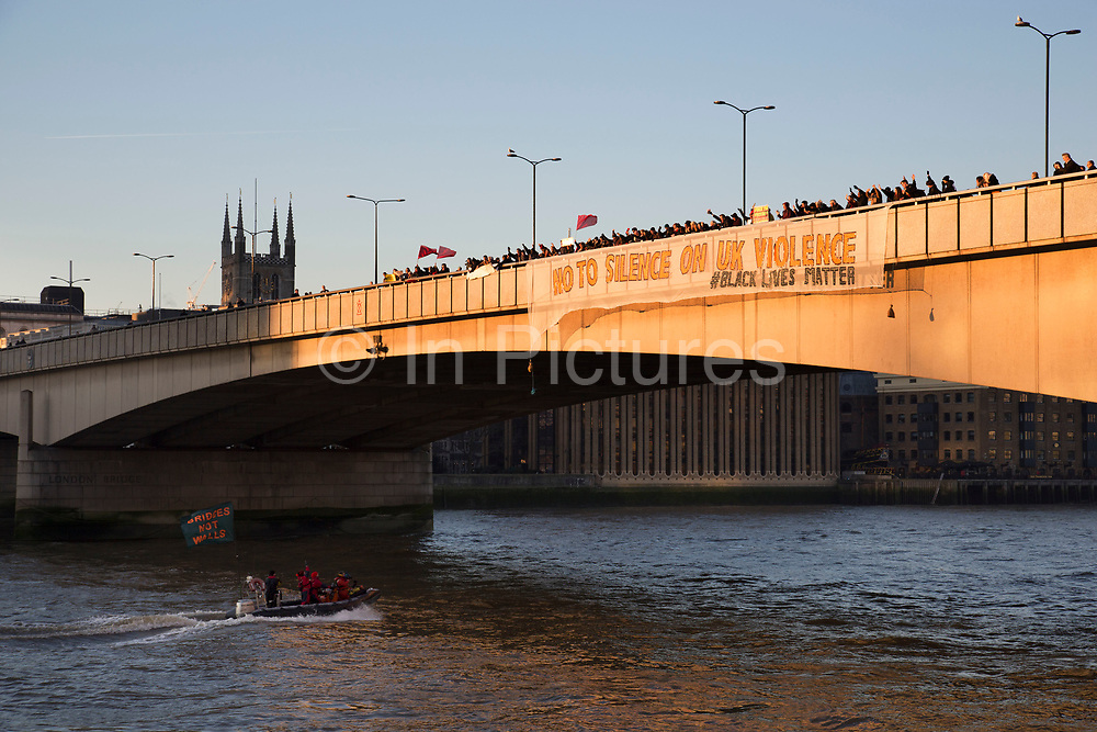Bridges not walls US Presidential inauguration day protest banners are dropped from London Bridge on 20th January 2017 in London, United Kingdom. Donald Trump was be inaugurated as the 45th President of the United States of America on this day and so in demonstration at some of the rhetoric, banners were dropped from bridges across the country to send a simple, hopeful and unmistakable message, to build bridges not walls for a peaceful and just World rid of oppression and hatred.