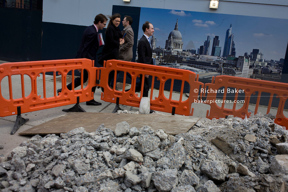 City workers walk past a pile of construction rubble near an skyline illustration of the City of London.