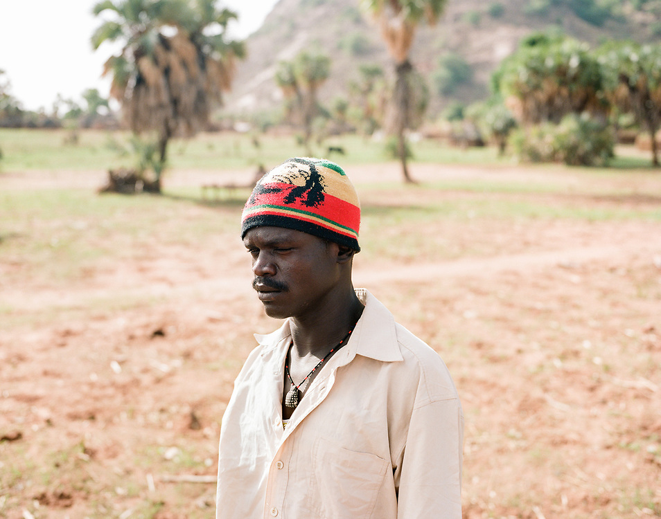 """NUBA MOUNTAINS, SUDAN – JUNE 7, 2018: Defected soldiers of the Sudan Armed Forces in the town of Kororak. After their capture and a subsequent period of imprisonment by the SPLA/M-N, the soldiers have been freed and now live independently among the Nuba, their former enemies.<br /> <br /> In 2011, the government of Sudan expelled all humanitarian groups from the country's Nuba Mountains. Since then, the Antonov aircraft has terrorized the Nuba people, dropping more than 4,080 bombs on hospitals, schools, marketplaces and churches. Today, vestiges of the Antonov riddle the landscapes of daily life, where more than 1 million Nuba live in famine conditions – quietly enduring the humanitarian blockade intended to drive them out of the region. The skies are mostly clear. Yet the collective memory of the bombings remains an open wound, and the Antonov itself a persistent threat. So frequent were the attacks that the Nuba nicknamed the high flying aircraft and its dismal hum: """"Gafal-nia ja,"""" they would declare, running to the hillsides. """"The loss of appetite has come."""""""