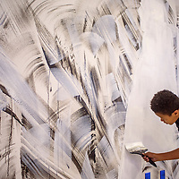 Josiah Montgomery adds his touch to a mural inside the new student union building during the Change Labs conference at Navajo Technical University in Crownpoint Friday.