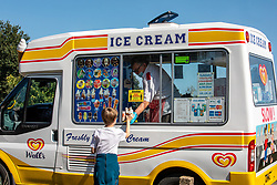 """© Licensed to London News Pictures. 13/09/2020. London, UK. A boy buys an ice-cream while enjoying the sunshine on Wimbledon Common in South West London this afternoon a day before the """"Rule of 6"""" comes into force on Monday as weather experts announce a 5 day mini-heatwave in the South East of England this week with highs of 29c. Prime Minister Boris Johnson announced on Friday that gatherings of more than six people will be banned from Monday (tomorrow) in the hope of reducing the coronavirus R number. The Rule of Six as it is known, has already become unpopular with MPs and large families for being too strict. Photo credit: Alex Lentati/LNP"""