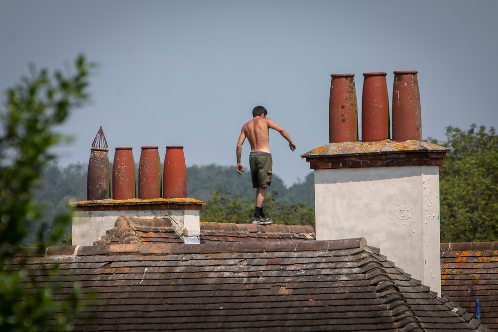 A male roofer walks along the peak of a house roof top on the 21st of July 2021 in Folkestone, Kent, United Kingdom. Roofing is one of the most dangerous professions, some roofers in the UK still work without the correct safety equipment. (photo by Andrew Aitchison / In pictures via Getty Images)