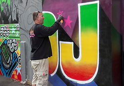 """© Licensed to London News Pictures; 11/08/2021; Bristol, UK. Street artist INKIE works on the finishing touches to a giant mural of DJ Derek on the side of a house by Junction 2 of the M32 motorway which will be passed by 150,000 vehicles a month. Two of the world's most famous street artists are among the team working on the tribute together, Bristol-based Harriet Wood, aka Hazard One has painted the image of DJ Derek, and Inkie is putting the finishing touches to the words and framing around the giant portrait. The project to create a lasting mural to DJ Derek began last year after a previous mural was tagged, and then painted over, to the dismay of family and friends. Artists, music fans and Derek's family came together with a fundraising campaign, that was then boosted by Arts Council backing. DJ Derek was born Derek Serpell-Morris (18 December 1941 – July 2015) and was an English DJ based in Bristol. In a DJ career that spanned over 40 years, he was known for playing a blend of 60s rocksteady, reggae, ska, dancehall and soul. He was reported missing in July 2015 and his remains were found near Cribbs Causeway on 10 March 2016 but police said they were not treating his death as suspicious. A former accountant at Cadburys, Derek began his DJ career in his mid-30s. He said he finished most sets with the Bob Marley hit """"One Love"""", saying it's a perfect signing-off record for a reggae set—let's get together and feel all right. He MCed in Jamaican Patois while DJing. Photo credit: Simon Chapman/LNP."""