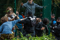Denham, UK. 7th September, 2020. A National Eviction Team enforcement agent tries to block activists from HS2 Rebellion seeking to prevent or delay tree cutting in conjunction with the HS2 high-speed rail link in Denham Country Park. Anti-HS2 activists continue to campaign and take direct action against the controversial £106bn project for which the construction phase was announced on 4th September from a series of protection camps based along the route of the line between London and Birmingham.