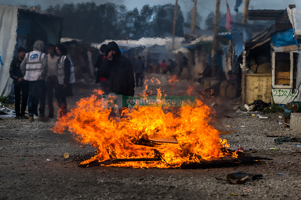 October 25, 2016 - Calais, France - A Migrant stands during the evection of the Calais Jungle behind a fire.  in Calais, France, on 25 October 2016 Up to the evening, about 4,000 migrants from the Refugee camp on the coast at the English Channel were distributed to several regions in France. The police have begun to tear down the huts and tents in the camp. (Credit Image: © Markus Heine/NurPhoto via ZUMA Press)