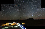 Vehicles and headlamps shine brightly under a starry night sky at a campsite below Factory Butte, near Hanksville, Utah.