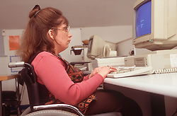 Woman with disability; who is wheelchair user; using computer in office,