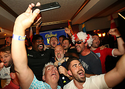 Dereck Chisora (left) with Fat Les (centre) as he performs at the Lord Raglan Pub in London.