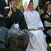 Asia, Japan, Okayama. Bride and Groom in traditional Japanese dress prepare to pose for wedding day photo of the extended family in the Korakuen Gardens.