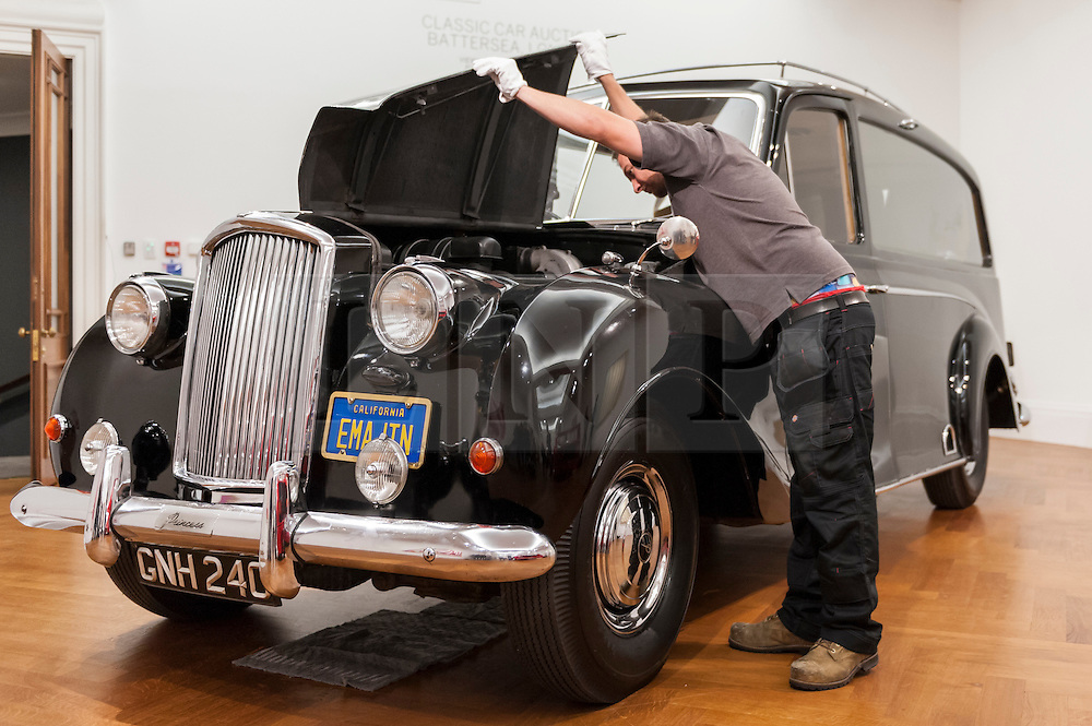 """© Licensed to London News Pictures. 12/08/2016. London, UK. A technician lifts the bonnet of John Lennon's iconic 1956 Austin Princess Limousine Hearse, immortalised in John Lennon and Yoko Ono's 1972 film """"Imagine"""" (est. GBP 250,000) at the photocall for classic cars at Sotheby's, New Bond Street, ahead of their auction on 7 September in Battersea Park. Photo credit : Stephen Chung/LNP"""