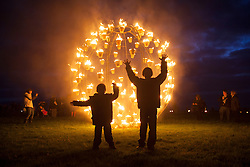 © licensed to London News Pictures. Wiltshire, UK 10/07/2012. Children posing with a fire sculpture at Stonehenge as they enjoy Fire Garden event which is part of the London 2012 Festival and Salisbury International Arts Festival. The heritage site surrounded with fire sculptures and fire posts by French outdoor fire alchemists Compagnie Carabosee. Photo credit: Tolga Akmen/LNP