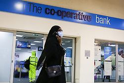 © Licensed to London News Pictures. 25/08/2020. London, UK. A woman wearing a face covering walks past a branch of Co-operative Bank in Wood Green, north London. As a result of an increase in people using online banking and the impact of coronavirus on the economy, Co-operative Bank announces that it plans to cut around 350 jobs and close 18 branches. The job losses will be focused on middle management positions and head office roles. Photo credit: Dinendra Haria/LNP