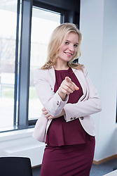 Portrait of businesswoman pointing towards beholder, smiling