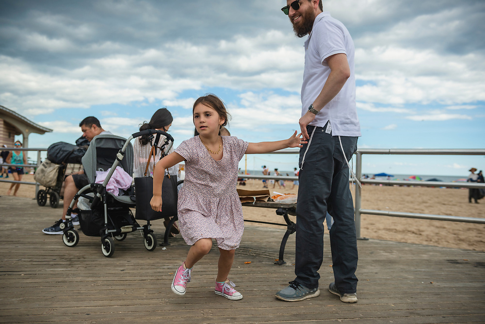 New York City, USA - July 10, 2016: Family on the boardwalk at Coney Island.