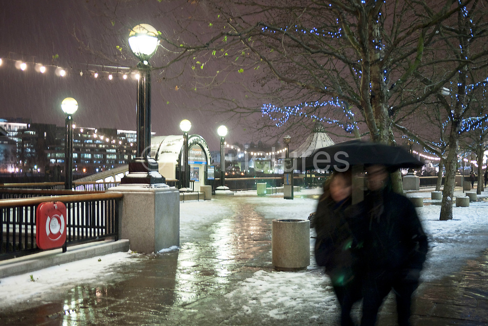 couple walk under an umbrella on a cold snowy winter evening.