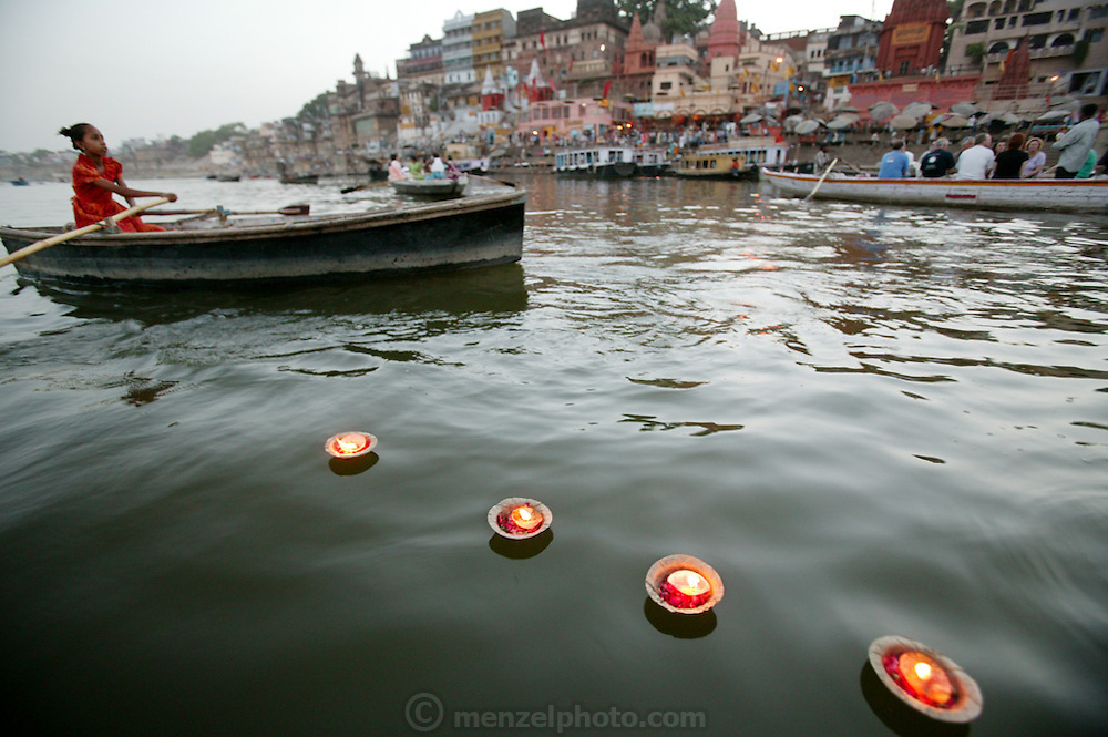 A young girl in a rowboad sells floating votive candles to mourners and also tourists near the Dashashwamedh Ghat, on the Ganges River in Varanasi, India.