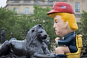 On US President Donald Trumps second day of a controversial three-day state visit to the UK, a Trump effigy tweets while sitting on a golden toilet opposite a lion at the foot of Nelsons Column in Trafalgar Square as protesters voice their opposition to the 45th American President, on 4th June 2019, in London England.
