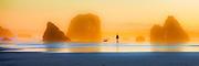 A man walks his  dog at Sunrise on Bandon Beach, OR