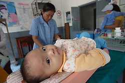 Unnamed child being weighed and then with Grandma, Sayaboury Provincial hospital, Sayaboury, Lao PDR.