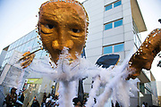 A woman in a three headed costume and white feathers dance along past the Hackney Library in East London, United Kingdom,Sept 11 2016. The annual Hackney Carnival took place on a hot summers day and the procession of dancers dressed in various outfits moved through the streets to much joy of the many bystanders.