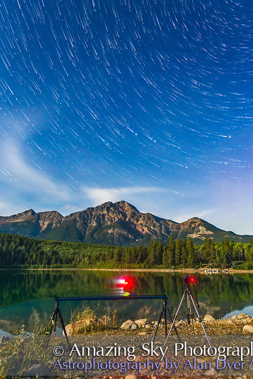 A star trail sequence shot at Patricia Lake in Jasper National Park, Alberta, showing two cameras at work shooting a time-lapse dolly motion control sequence (at left) and a static camera star trail sequence (at right). This is a stack of 100 frames out of 400 shot by the third camera, with one frame shot a couple of minutes after the sequence and layered in to add the blurry but point-like stars at the ends of the trails, including the Big Dipper. Each frame was 32 seconds at f/4.5 (stopped down too much by accident) with the 24mm lens at Canon 6D at ISO 800 in bright moonlight from the waxing gibbous Moon.