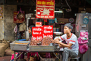 11 SEPTEMBER 2013 - BANGKOK, THAILAND:  A man selling chestnuts at a street stall in the Chinatown section of Bangkok. Thailand in general, and Bangkok in particular, has a vibrant tradition of street food and eating on the run. In recent years, Bangkok's street food has become something of an international landmark and is being written about in glossy travel magazines and in the pages of the New York Times.        PHOTO BY JACK KURTZ