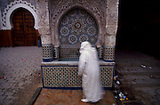 "Man wearing a traditional ""jelaba"" clothing near a fountain close by Attarine Medersa."