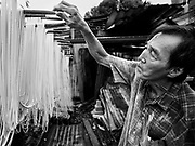 """29 DECEMBER 2018 - BANGKOK, THAILAND: A man hangs longevity noodles out to dry in front of his family shophouse. The family has been making traditional """"mee sua"""" noodles, also called """"longevity noodles"""" for three generations in their home in central Bangkok. They use a recipe brought to Thailand from China. Longevity noodles are thought to contribute to a long and healthy life and  are served on special occasions, especially Chinese New Year, which is February 4, 2019. These noodles were being made for Chinese New Year.    PHOTO BY JACK KURTZ"""
