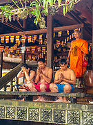 Three people receive a water blessing from a monk at a Cambodia Buddhist temple during the Water Festival. Angkor Wat Archeological Park, Siem Reap, Cambodia.