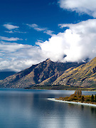 Walter Peak in the clouds and Lake Wakatipu, one of New Zealand's most beautiful lakes, surrounded by mountains and set off by clouds and blue sky on an autumn day.