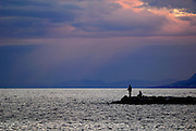Two people fishing from rocks after sunset. Makarska, Croatia