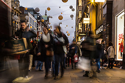 London, December 24 2017. Crowds grow in London's west end on Christmas eve as last minute shoppers hunt for gifts. PICTURED: Shoppers make their way along Oxford Street as daylight fades. © SWNS